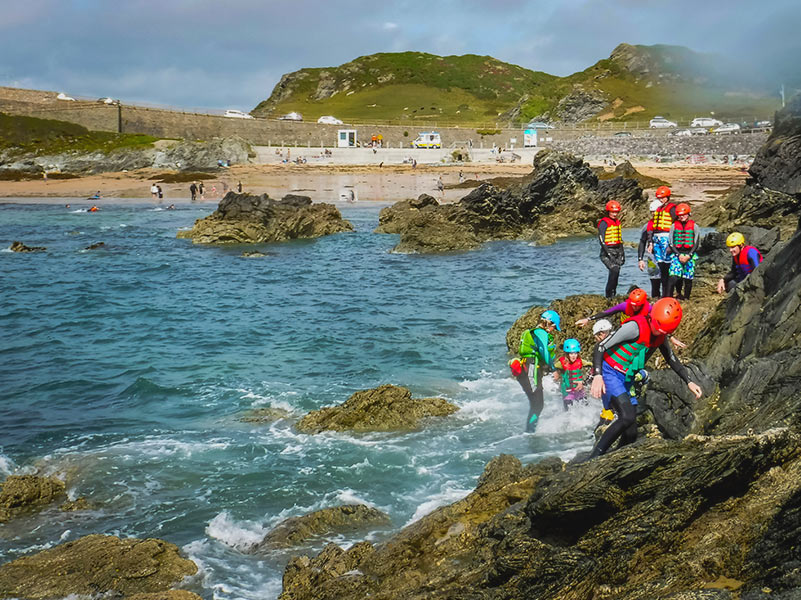 Group of people coasteering in Porth Dafarch Bay