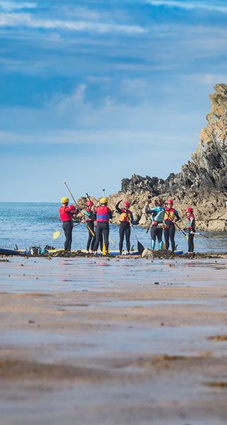 A group of paddle boarders preparing to headout at Porth Dafarch Beach