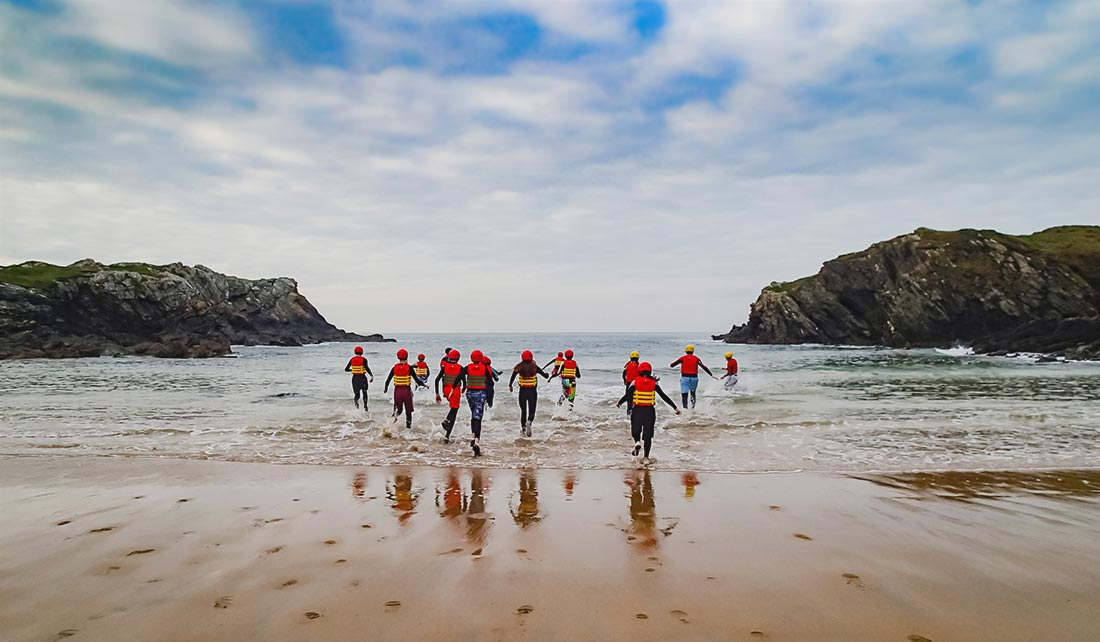 Group of people coasteering running into Porth Dafarch sea water