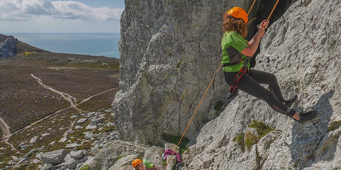 Man hanging over a cliff on a rock climbing course in Anglesey