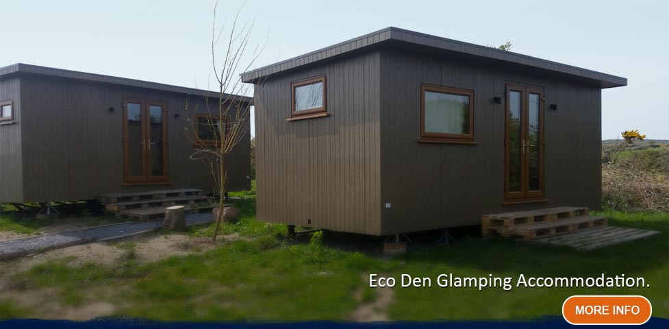 Two brown eco den glamping units on grass verge